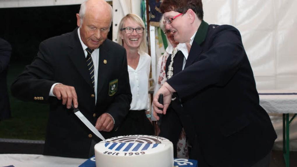 Ernst-Günther Löwe und Heide Brodda schneiden die Torte mit dem neuen Logo des SV Wallsbüll an. - Foto: Helga Böwadt
