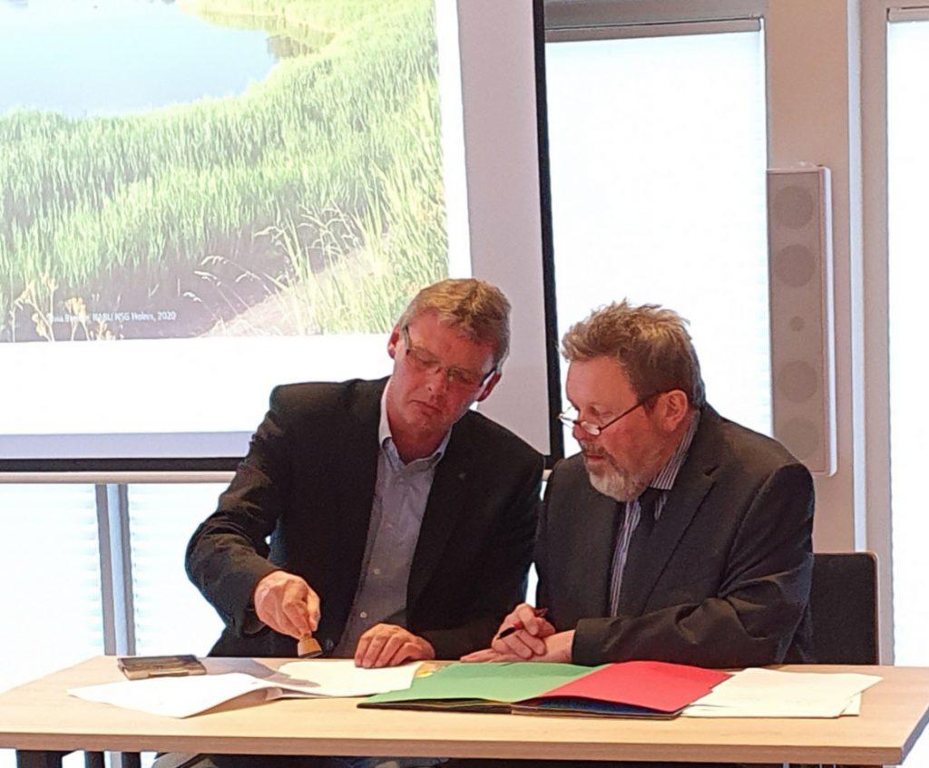 Links Arno Asmus, Bürgermeister aus Wallsbüll, daneben Burkhard Gerling beim unterzeichnen des Förderbescheids